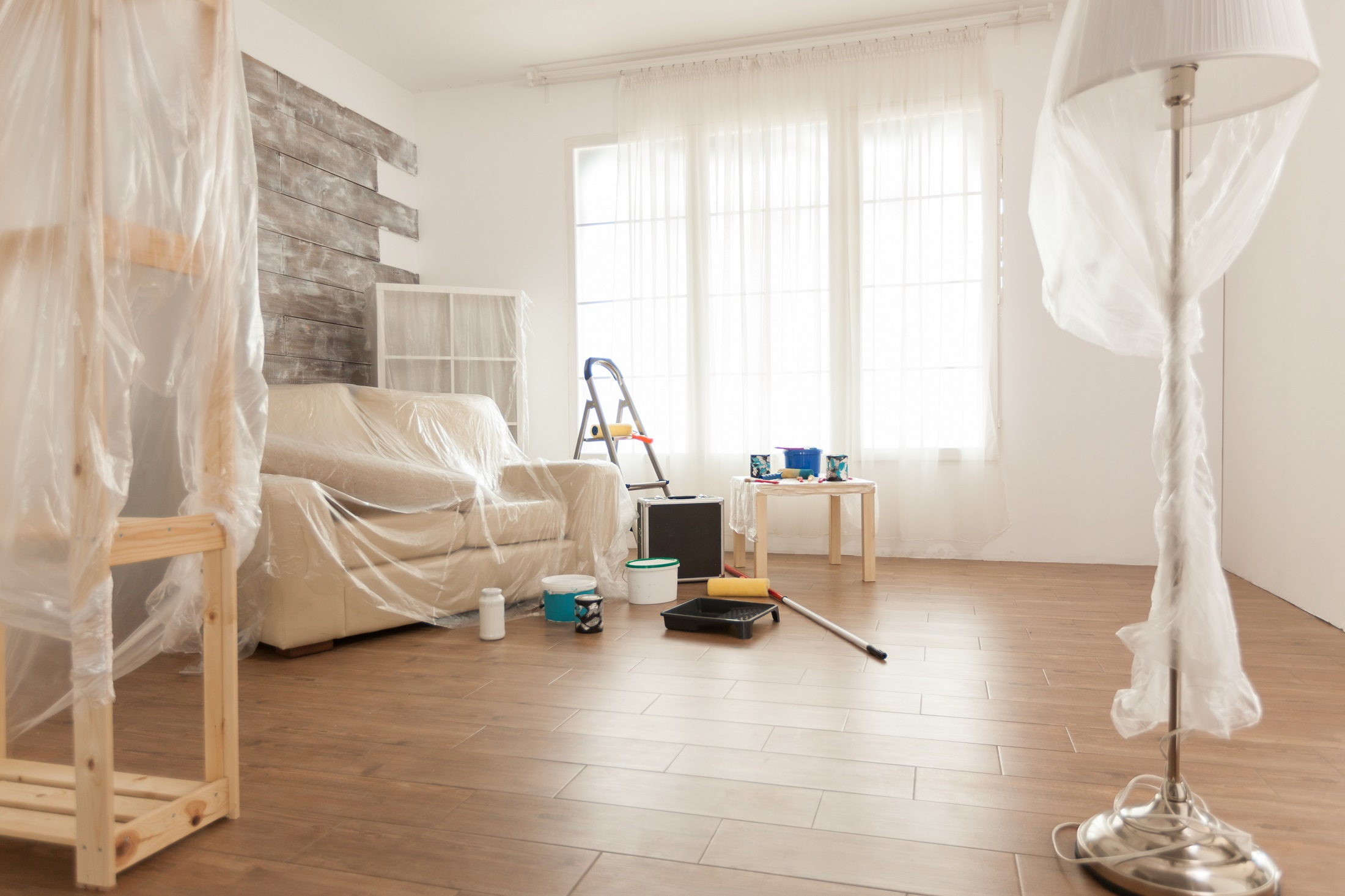 Apartment with nobody in it ready for professional renovation. Plastic sheet. Home during renovation, decoration and painting. Interior apartment improvement maintenance. Roller, ladder for house repair