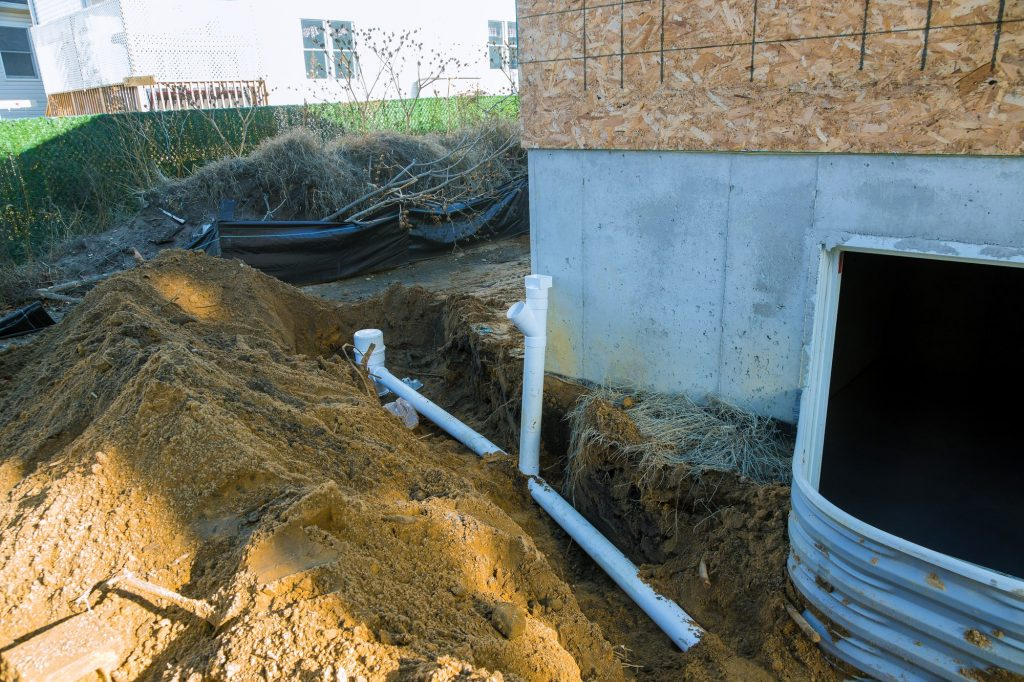 Plastic piping and a rainpipe against and around the a drain pipe in ground house